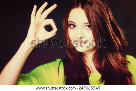 Happy successful young people concept. Satisfied positive teen girl showing ok sign hand gesture on black - stock photo