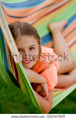 Happy summer holiday - lovely girl in colorful hammock - stock photo