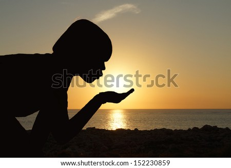 Happy summer photo of young boy making a wish by blowing the setting sun from his hands