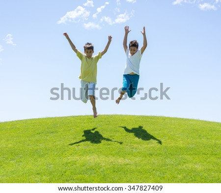 Happy summer vacation for kids on green meadow near sea - stock photo