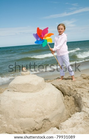 Happy summer vacation - girl playing with pinwheel on sandy beach
