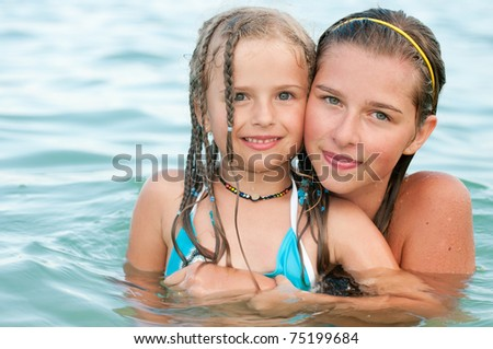 Happy summer vacation - happy girls in the sea - stock photo