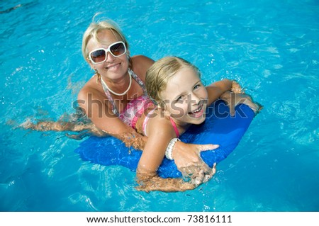 Happy summer vacation - little girl with mother boarding in blue water - stock photo
