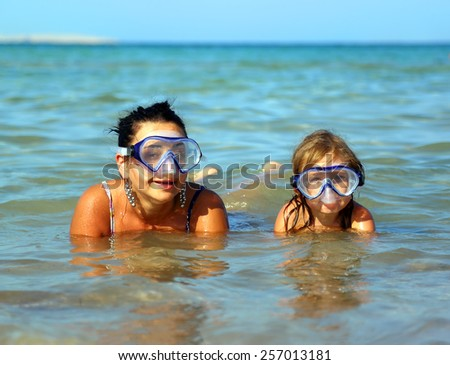 Happy summer vacation - snorkeling daughter with mother - stock photo