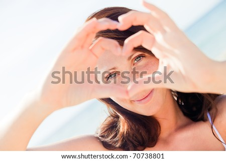Happy summertime woman smiling on the beach making love heart symbol - stock photo