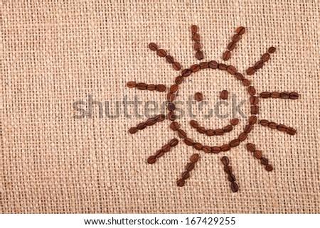 Happy sun of coffee beans on burlap background  - stock photo