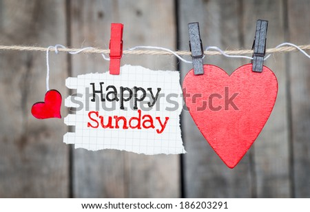 Happy Sunday on instant paper and small red hearts hanging on the clothesline. On old wood background - stock photo