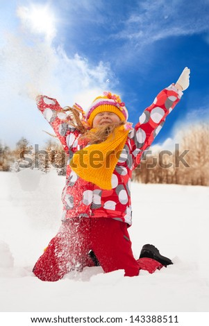 Happy supper exited girl throwing snow in the air on sunny day - stock photo