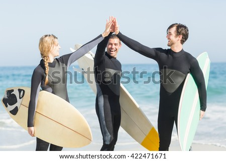 Happy surfer giving high-five to each other on the beach on a sunny day - stock photo