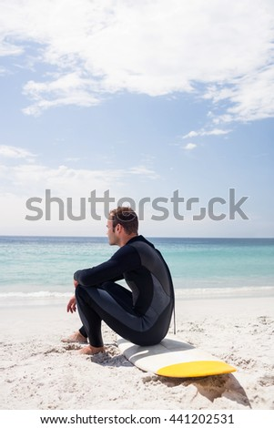 Happy surfer in wetsuit sitting with surfboard on the beach on a sunny day - stock photo