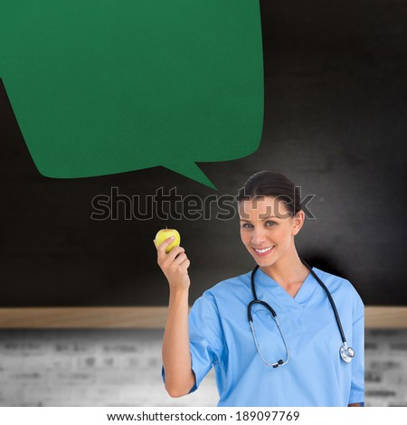 Happy surgeon holding an apple with speech bubble against blackboard on wall - stock photo