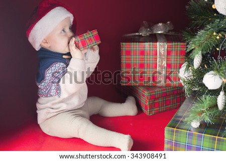 Happy surprised baby holding gift box or present at Christmas night, eve! Kid dressed in red Santa hat. Xmas and New Year holiday! Teeth itch - stock photo