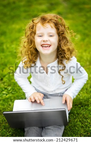 Happy surprised child with laptop sitting on the grass. - stock photo