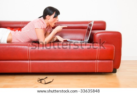 Happy surprised internet brwosing woman showing finger thumb to laptop screen while lying at home on red couch - stock photo