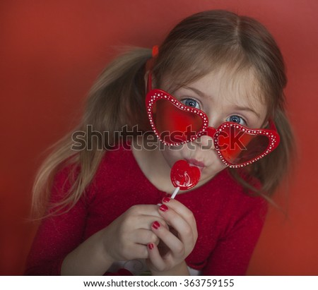 Happy sweet girl in sunglasses with lollipop. Valentineâ??s day