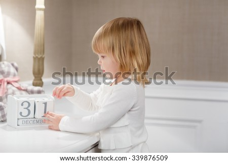 Happy sweet little girl  with date 31 december stands in the room . Eve of New Year. - stock photo