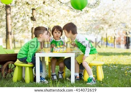 Happy sweet preschool children, friends and relatives, celebrating fifth birthday of cute boy, outdoor in blooming apple tree garden, springtime, late afternoon - stock photo