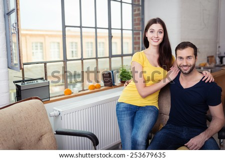 Happy Sweethearts Posing Near the Window at the Living Room While Looking at the Camera - stock photo