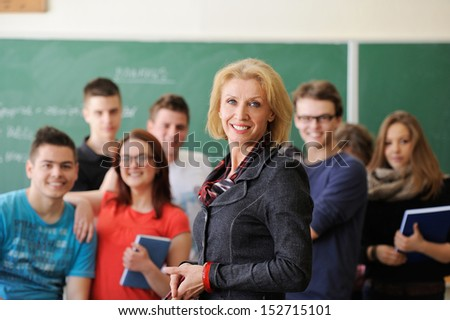 Happy teacher and a group of students in front of a chalkboard - stock photo