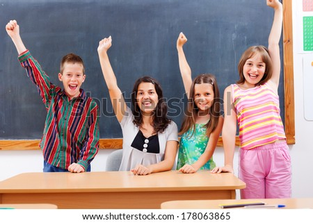 Happy teacher and her students classroom with raised hands