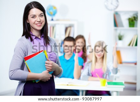 Happy teacher looking at camera with her students on background - stock photo
