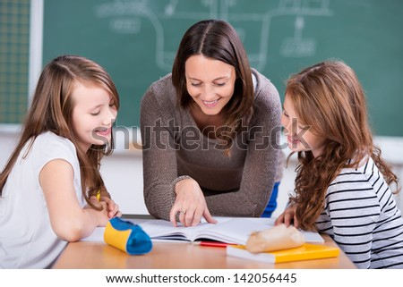 Happy teacher teaching her two students inside the school