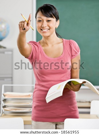 Happy teacher with text book gesturing and asking questions in school classroom