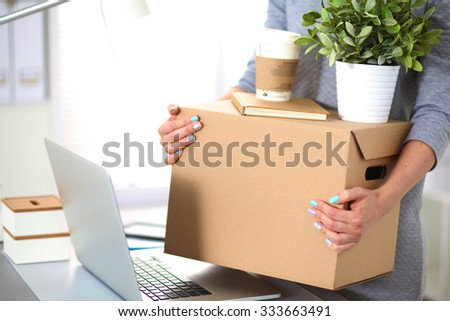 Happy team of businesspeople moving office, packing boxes, smiling - stock photo