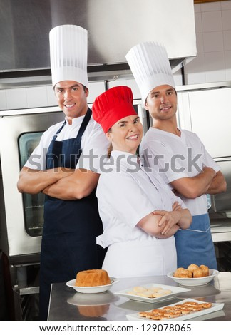 Happy team of confident chefs with sweet dishes on commercial kitchen counter - stock photo