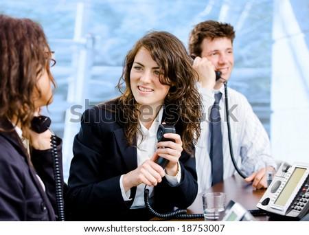 Happy team of customer service operators calling on phone. - stock photo