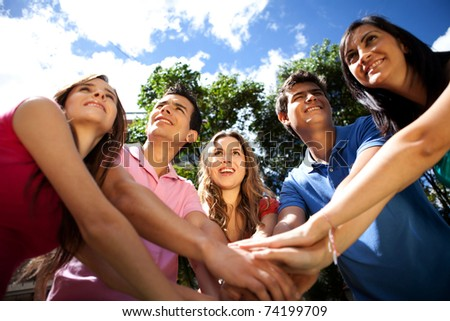 Happy team of people with hands together outdoors - stock photo