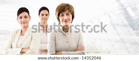 Happy team of three businesswomen standing in front of windows inside officebuilding, smiling. Business banner. - stock photo