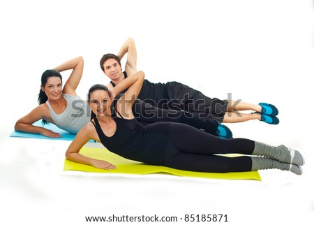 Happy team of three fitness people doing exercises on colorful mats against white background - stock photo