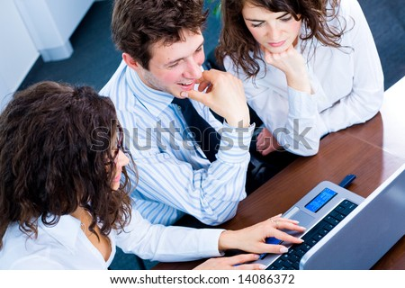 Happy team of young business people sitting in meeting room, working together on laptop computer, smiling. Overhead view. - stock photo