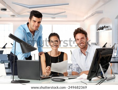 Happy team of young business people working together in office. - stock photo