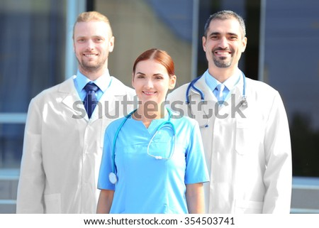Happy team of young doctors standing against hospital entrance - stock photo