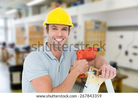 Happy technician holding drill machine while leaning on ladder against workshop - stock photo