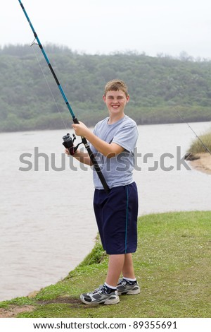 happy teen boy fishing by the lake - stock photo