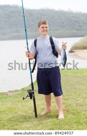 happy teen boy holding fishing rod and a fish he caught - stock photo