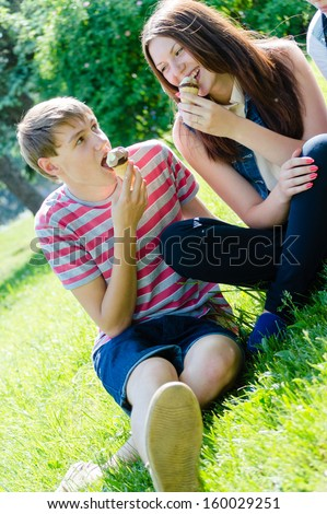 Happy teen couple eating ice cream on sunny summer day outdoors background - stock photo