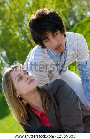 Happy teen couple flirting in the park