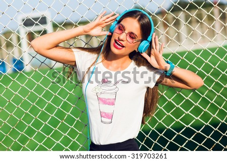 Happy teen cute cheerful  girl   listening to music and enjoying  it so much. Wearing stylish  summer clothes and blue earphones. Pink sunglasses. Bright  summer colors. - stock photo