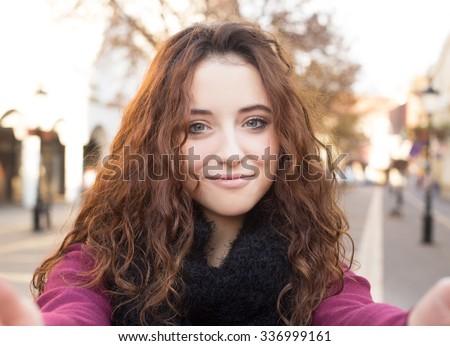 happy teen girl doing selfie photo on street in autumn - stock photo