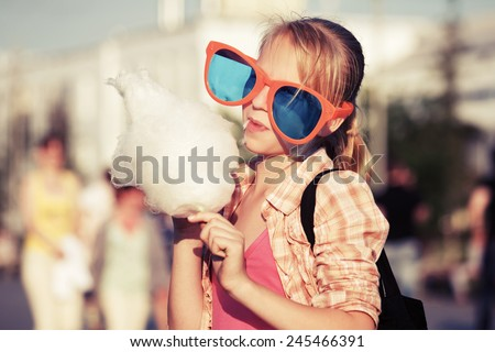 Happy teen girl eating cotton candy on the city street - stock photo