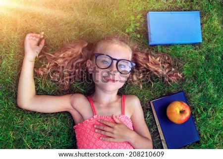 Happy teen girl in nature with a book  - stock photo