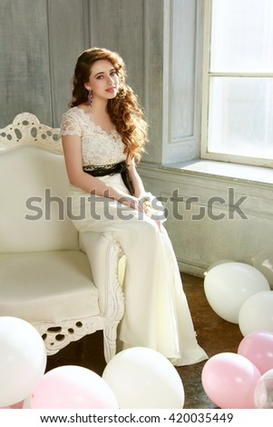 Happy teen girl in prom look in beautiful interior with air balloons - stock photo