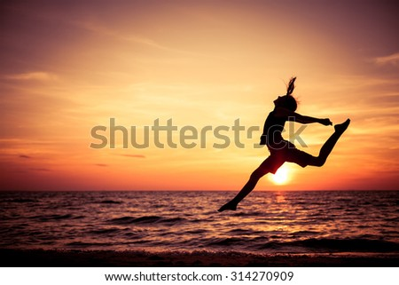 Happy teen girl  jumping on the beach at the sunset time - stock photo