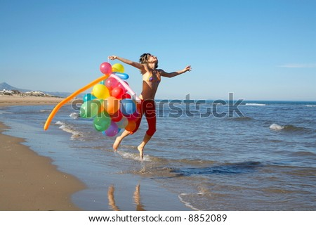 happy teen girl jumping on the beach with different colored balloons