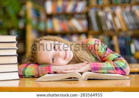 Happy teen girl lying on table in library - stock photo