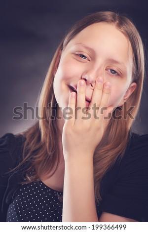 Happy teen girl making funny faces, studio shot - stock photo